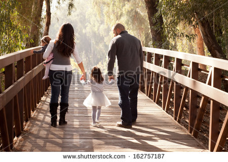 stock-photo-happy-family-walking-away-towards-a-forest-on-an-old-wooden-bridge-mother-father-two-daughters-162757187