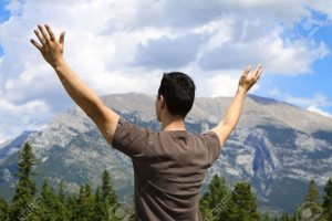 7483903-Man-standing-in-nature-with-arms-lifted-up-Stock-Photo-worship-christian-hope