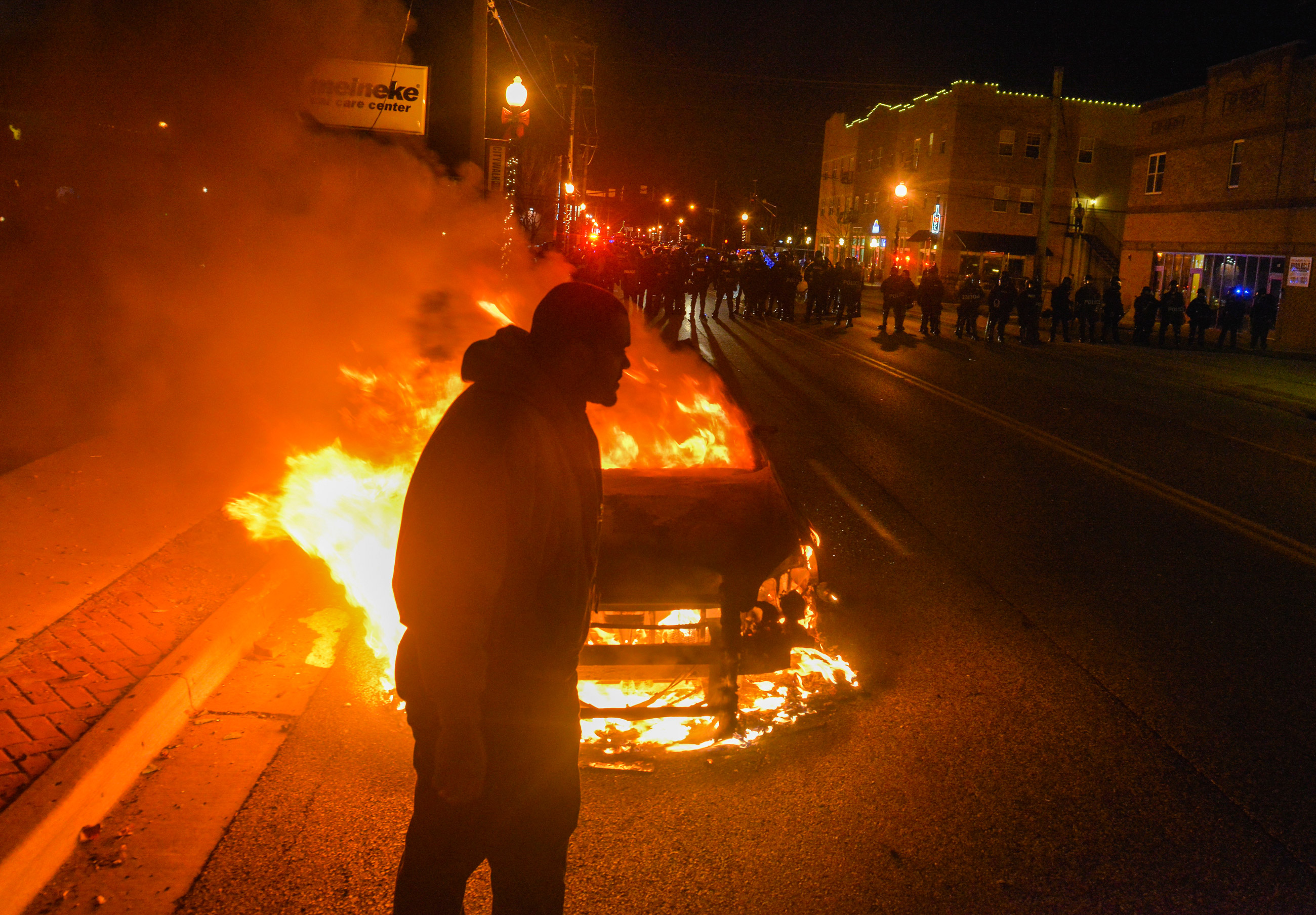 FERGUSON, MO - NOVEMBER 24: A man makes his way past a burning police car as a line of officers prepare to clear the street of protesters after an announcement that Ferguson police officer Darren Wilson will not be indicted in the fatal shooting of unarmed teenager Michael Brown, on Monday, November 24, 2014, in Ferguson, MO.  The shooting of Michael Brown, an unarmed black 18-year-old by white Ferguson police officer Darren Wilson, has captivated the nation as a grand jury deliberated to decide whether to charge the officer with a crime.   (Photo by Jahi Chikwendiu/The Washington Post)