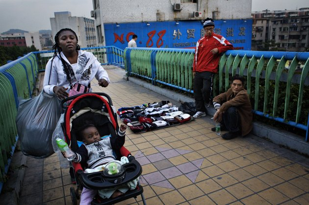 GUANGZHOU, CHINA - DECEMBER 13:  An African woman with a baby in a stroller pass a pedestrian bridge where Chinese street vendors aretrying to attract customers December 13, 2008 in Guangzhou, China. In Guangzhou, the largest city in south China, 20.000 Africans are trying to make a life for themselves as traders in wholesale markets. Here, they hope to carve out their own piece of the Chinese economical miracle. The traders buy clothes and other cheap goods to be shipped and sold back home. Approximately 80% of the Africans in Guangzhou are Nigerians, others are from e.g. Ghana, Kenya and Cameroon.  (Photo by David Hogsholt/Getty Images)
