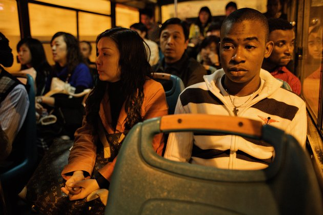 GUANGZHOU, CHINA - DECEMBER 17:  African trader Nelson sits on a bus taking him home December 17, 2008 in Guangzhou, China. In Guangzhou, the largest city in south China, 20.000 Africans are trying to make a life for themselves as traders in wholesale markets. Here, they hope to carve out their own piece of the Chinese economical miracle. The traders buy clothes and other cheap goods to be shipped and sold back home. Approximately 80% of the Africans in Guangzhou are Nigerians, others are from e.g. Ghana, Kenya and Cameroon.  (Photo by David Hogsholt/Edit by Getty Images)