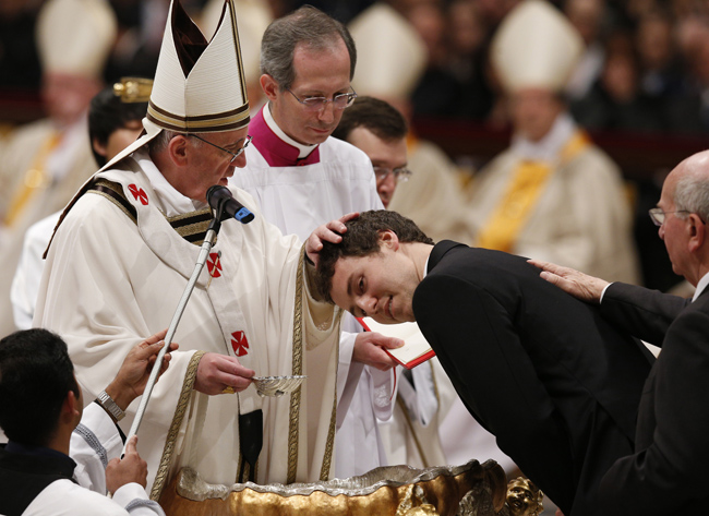 Pope Francis baptizes a young man during the Easter Vigil in St. Peter's Basilica at the Vatican March 30. (CNS photo/Paul Haring) (March 31, 2013) See FRANCIS-EASTER March 31, 2013.
