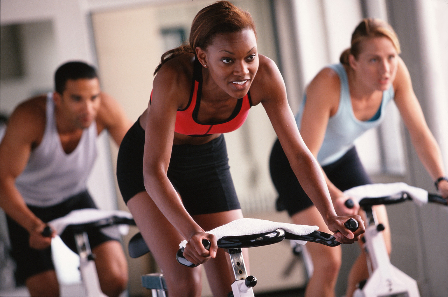 Three adults riding exercise bikes in gym (selective focus)