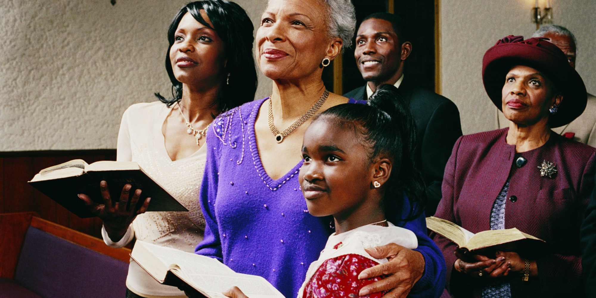 Family Standing in Church Pews Holding Bibles and Listening to a Service