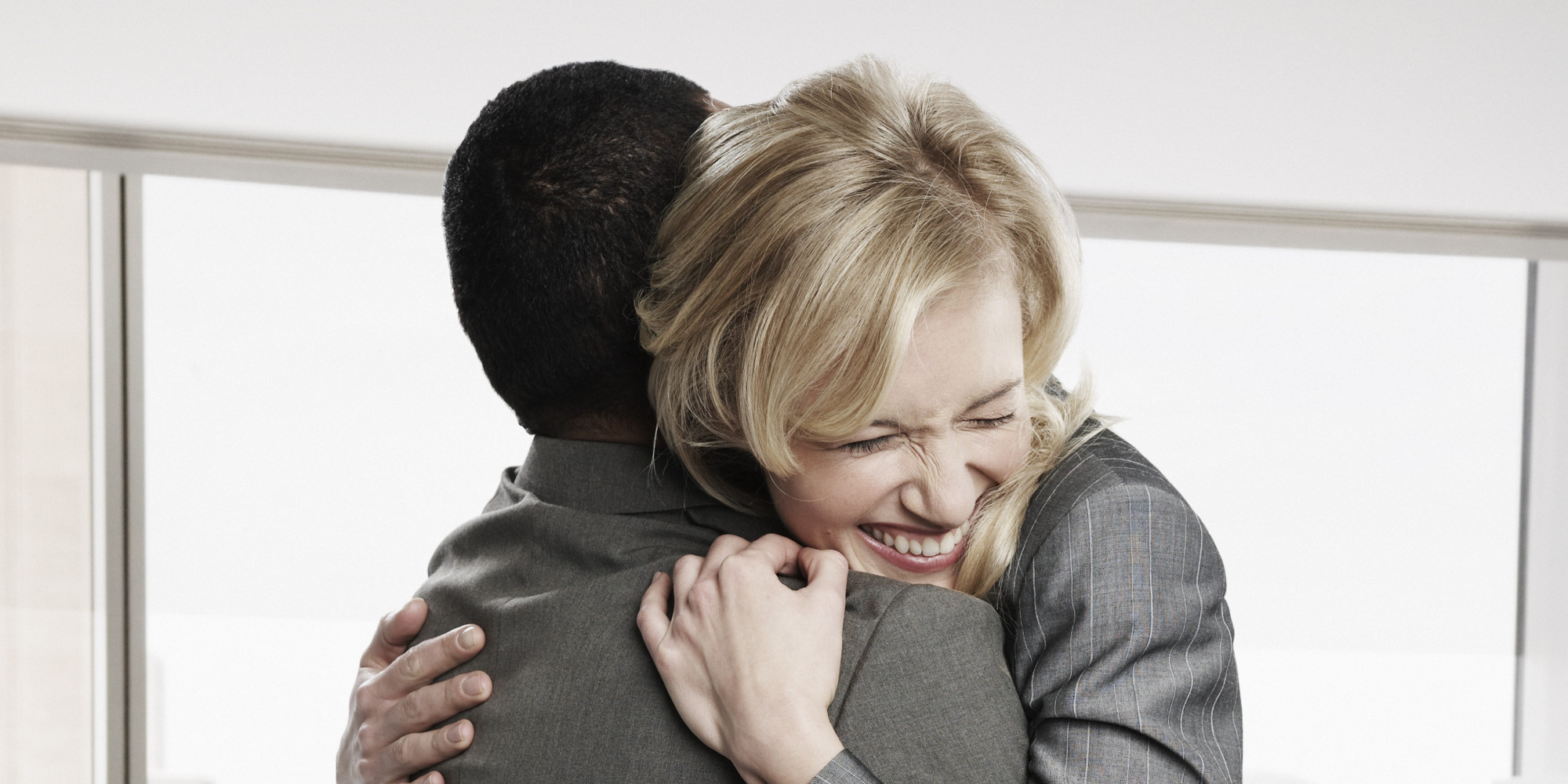 Two business people hugging in office